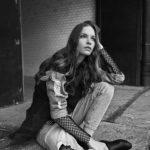 Czarno-białe zdjęcie dziewczyny siedzącej na ziemi