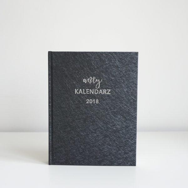 Na szarym tle czarny kalendarz z wytloczonym napisem Anty Kalendarz