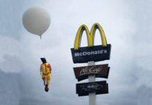 Ronald McDonald wiszacy na logo Mc Donalds
