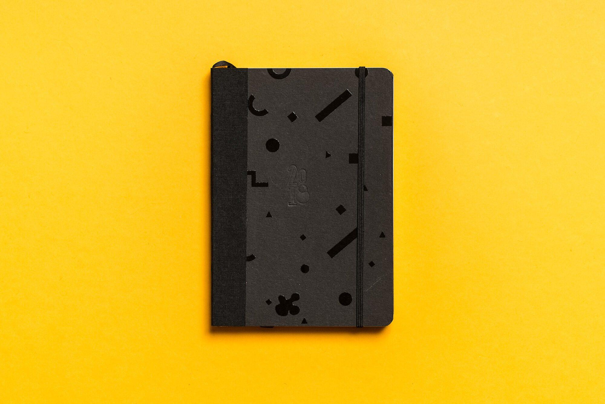 Czarny kalendarz z czarnymi geometrycznymi figurami na zoltym tle
