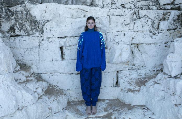 Dziewczyna ubrana na niebiesko stojąca na tle białej ściany
