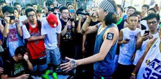 Grupa ludzi na ulicy, w środku mężczyzna z mikrofonem