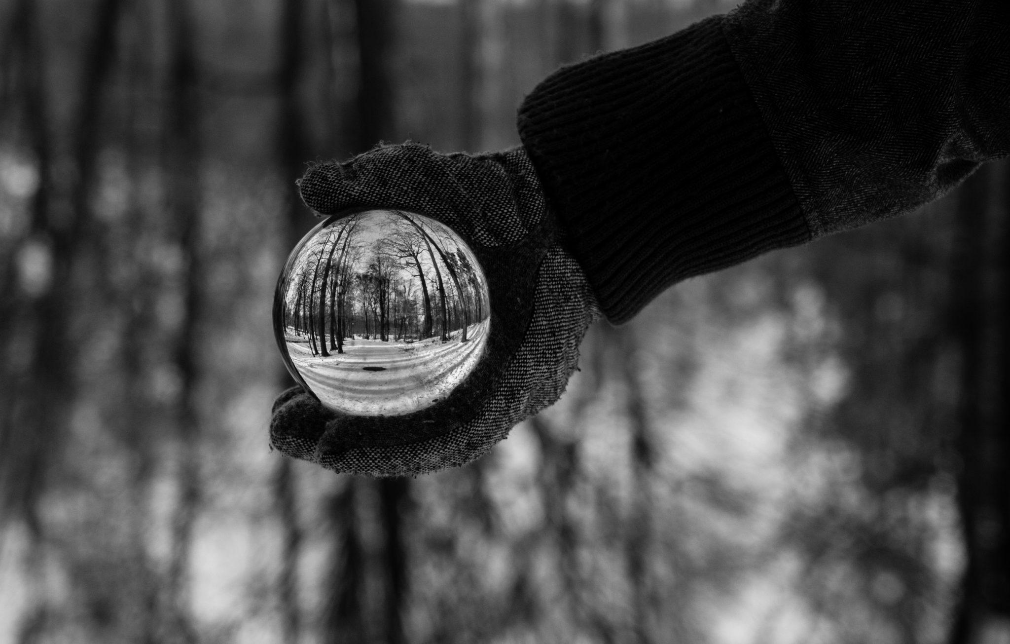 Krzyształowa kula trzymana w wyprostowanej ręce, a całe zdjęcie czarno-białe