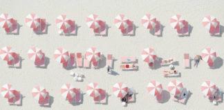 zdjecie plazy zrobione z nieba, przedstawiajaca wiele roznych bialo rozowych parasoli