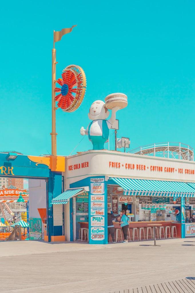 zdjecie przedstawiajace kolorowa ulice z kolorowoymu jasnymi sklepami i restauracjami