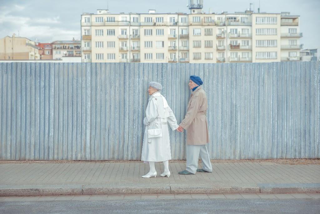 para starszych ludzi strzymajacych sie za reke stojacych na chodniku