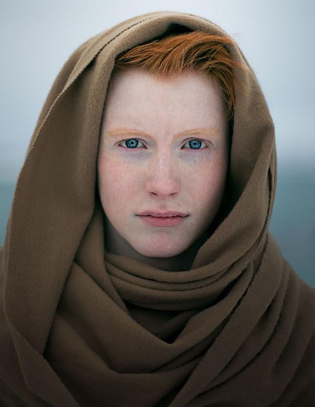 porter rudowlosej kobiety z piegami na twarzy, jest zakapturzona w materialowa,brazowa chuste