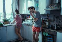 Kobieta stojąca przy oknie i mężczyzna opierający się o kuchenny blat z papierosem w ustach