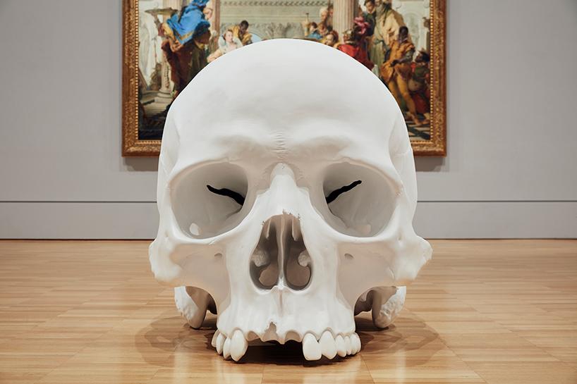 1,5 - metrowa czaszka ujęta z przodu, stojąca na podłodze. W tle widać ścianę i obraz wiszący na scianie galerii.