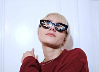 Blondynka z czerwonym swetrze i migoczących okularach