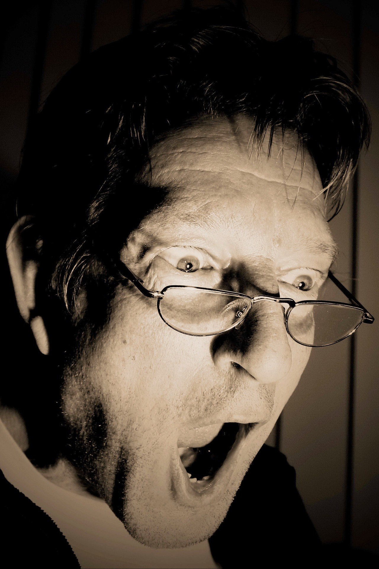 Mężczyzna wpatrzony w coś z okularami na nosie i szeroko otwartą ze zdziwienia buzią