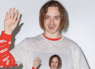 Mężczyzna w szarej bluzie z podniesioną w geście machania ręką