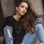 Dziewczyna w jeansach z dziurami i w czarnej bluzce siedzi na ziemi