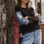 Dziewczyna w jeansowych spodniach i bluzce oparta o ścianę