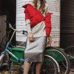 Dziewczyna stojąca na wysokości słupa z ogłoszeniami, za nią rower