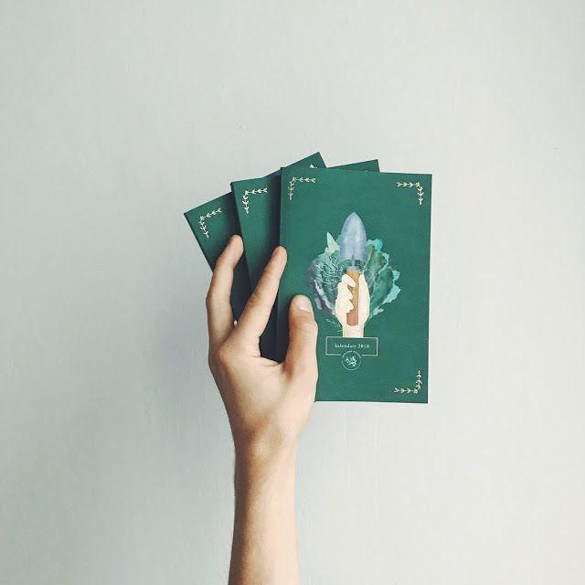 Na siwym tle dlon trzymajaca trzy zielone kalendarze na okladce widzimy lopate