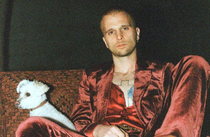 Mężczyzna w czerwonym garniturze z białym psem obok