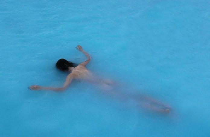 Dziewczyna leżąca na brzuchu na tafli wody