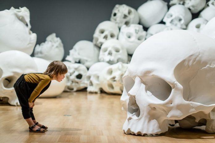 Dziecko w żółtej bluzce, czarnych ogrodniczkach i czarnych sandałach uchwycone z boku pochyla się przed 1,5-metrową czaszką i zagląda jej w oczodoły. Ręcę trzyma na kolanach. W tle widać kilka czaszek.