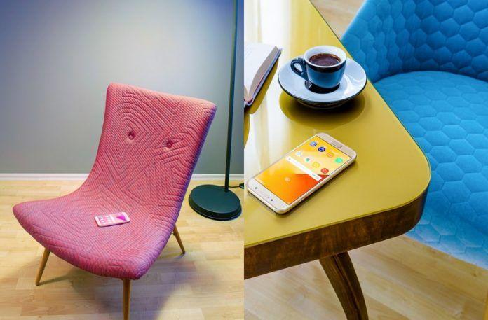 Różowy fotel z telefonem i żółty stolik z niebieskim fotelem