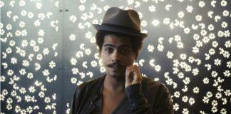 Mężczyzna w marynarce i kapeluszu na tle świecącej ściany