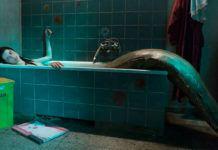 Dziewczyna z syrenim ogonem leży w wannie. Na podłodze leży ilustracja kota. Łazienka i wanna są wykonane z błekitnych kafelek.