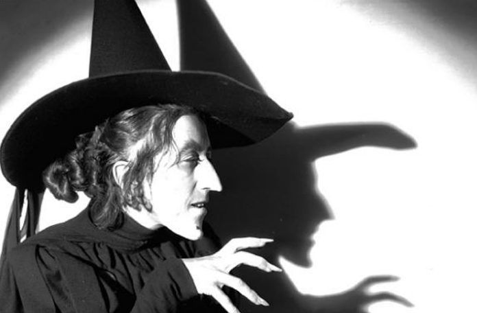 Czarno-białe zdjęcie przedstawiające stojącą profilem Wiedźmę