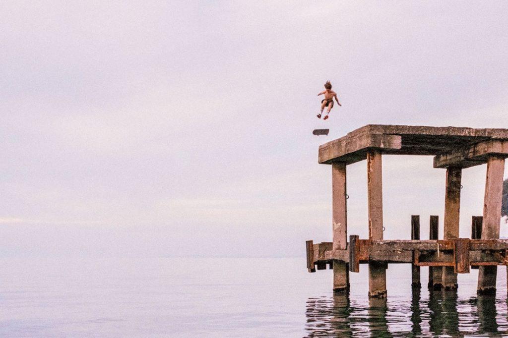 kobieta skacze do wody z betonowego rusztowania