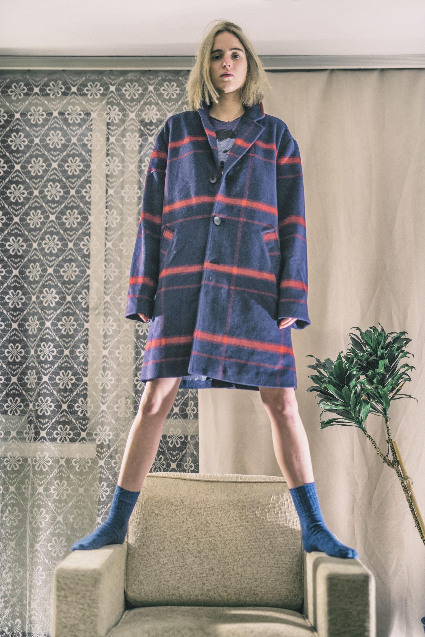 na zdjeciu widzimy mloda dziewczyne ubrana jedynie w niebieska marynarke w czerwone paski typu oversize i niebieskie skarpetki na stole w tle widzimy prlowskie mieszkanie firany okno i rosline
