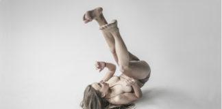 Kobieta leżąca na ziemi z nogami w górze