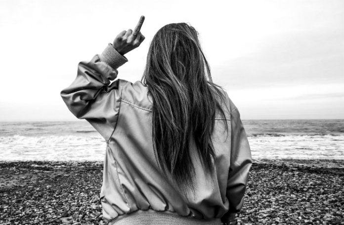 Czarno-białe zdjęcie przedstawiające dziewczynę pokazującą środkowy palec