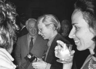 Czarno-białe zdjęcie przedstawiające mężczyzne trzymajacego aparat i kobiety ze szklanką przy ustach