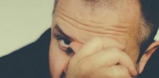 Mężczyzna zakrywający twarz ręką