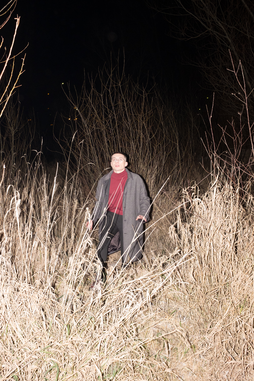 Zdjecie jest zrobione noca z lampa swietlna pomiedzy zborzami miedzy zdblami mozna dostrzec postac mlodego chlopaka w okularach ubranego w szary rozpiety plaszcz czerwony golf i ciemne spodnie