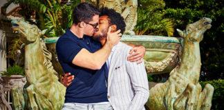 Dwóch mężczyzn w garniturach całujących się przy fontannie