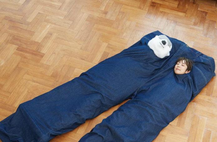 Dziewczyna śpiąca w śpiworze, który wygląda jak gigantyczne jeansy