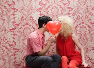 Para schowana za balonem w kształcie serduszka
