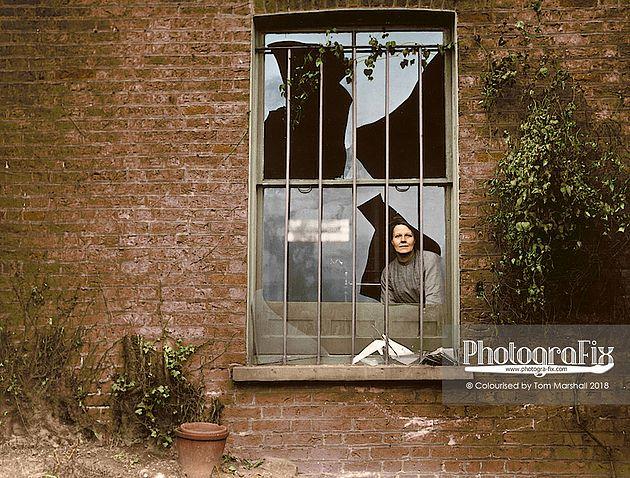 Kobieta stojąca za potłuczoną szybą okna