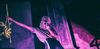 Na zdjeciu widzimy dziewczyne ubrana w leginsy i tshirt, ktora w jednej rece trzyma mikrofon a w druga wymachuje w lewo jest na scenie tylnia sciana jest oswietlona na rozowo