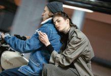 Dziewczyna jadąca z chłopakiem na motorze z papierosem w dłoni