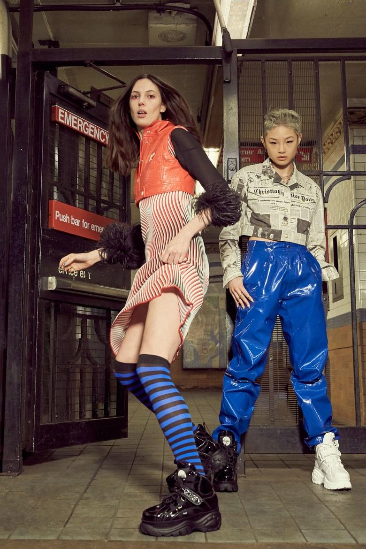Dwie kobiety stojace przed brama jedna w spodnicy druga w spodniach
