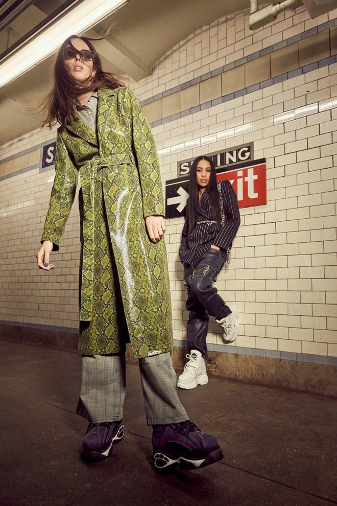 Dwie kobiety stojace w podziemiach metra pierwszoplanowa ubrana jest w zielony plaszcz i okulary przeciwsloneczne druga oparta o sciane