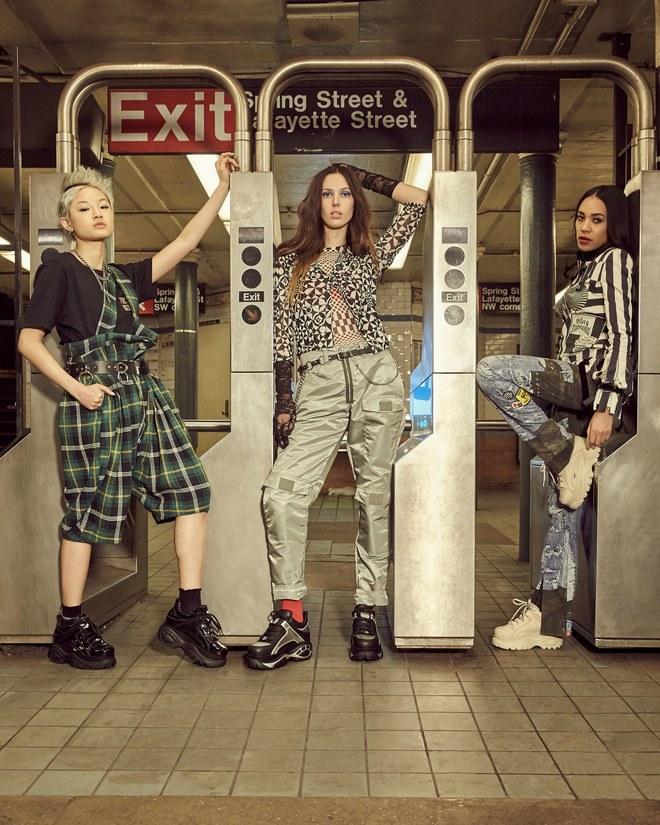 Trzy kobiety stojace przy wejsciu do metra