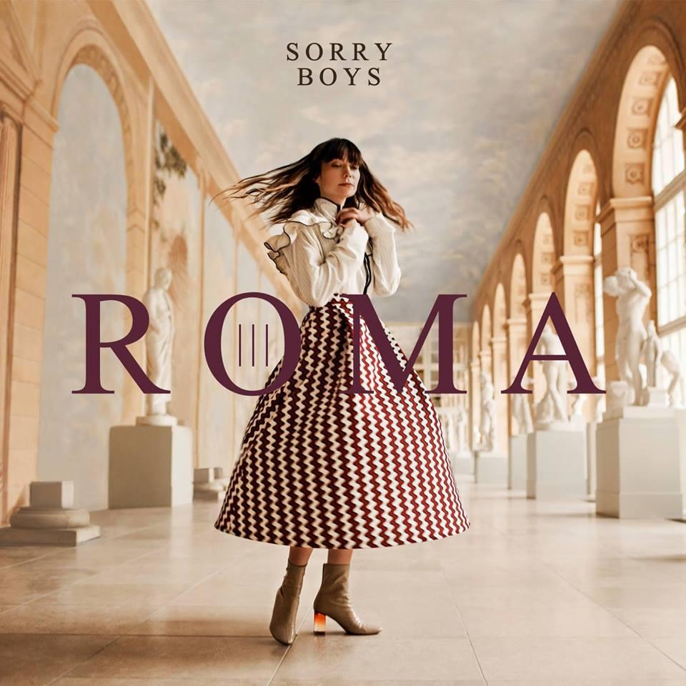 Okladka plyty kobieta brunetka w dlugich wlosach pozuje w ruchu ubrana w dluga spodnice w czerwono biale paski i biala koszule pozuje w starozytnym wnetrzu na srodku jest napis roma