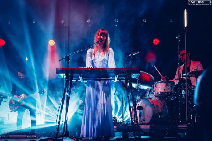 Dziewczyna w białej sukience stojąca przy klawiszach