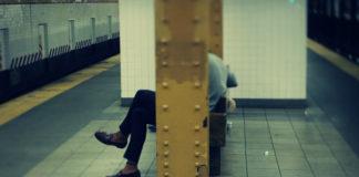 Człowiek siedzący na stacji metra z twarzą zasłoniętą przez barierkę