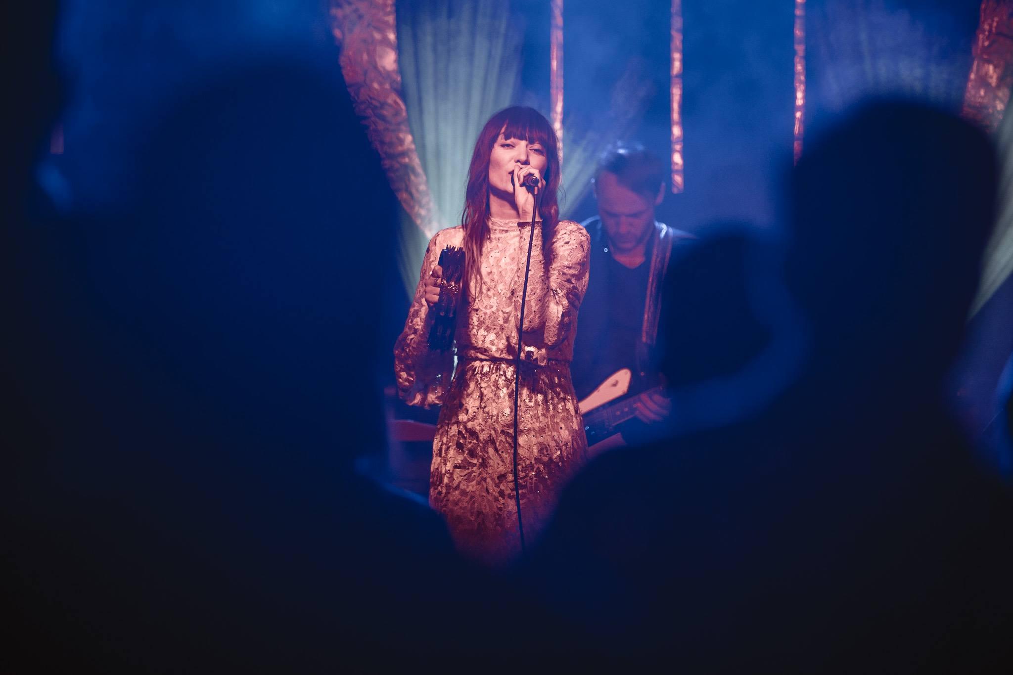 Zdjecie przedstawia koncert na pierwszym planie widzimy cienie rozmazanych widzow jedynie wokalistka kobieta ubrana w rozowa sukienke z mikrofonem brunetka w dlugich wlosach trzyma mikrofon za nia widzimy rozmazanego gitarzyste