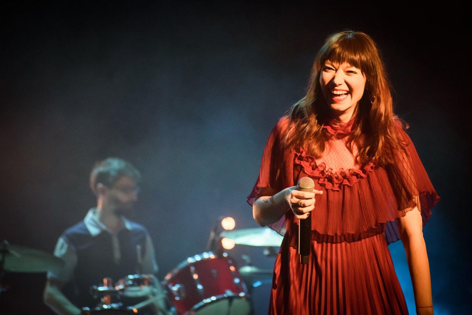 Na zdjeciu widzimy koncert w tle lekko rozmyty jest perkusista z broda a na pierwszym planie kobieta w dlugich wlosach usmiechnieta trzyma mikrofon ubrana jest w czerwona sukienke
