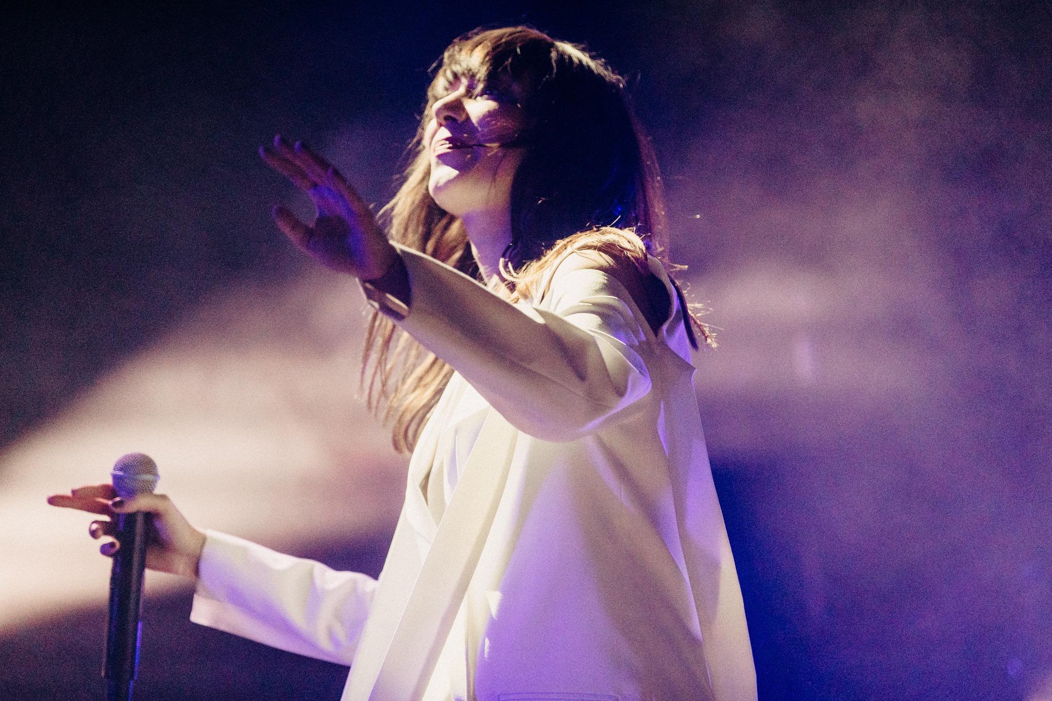 Zdjecie przedstawia koncert widzimy fioletowe swiatlo a na jego tle do polowy kobiete brunetke ubrana w biala marynarke ma dlugie wlosy