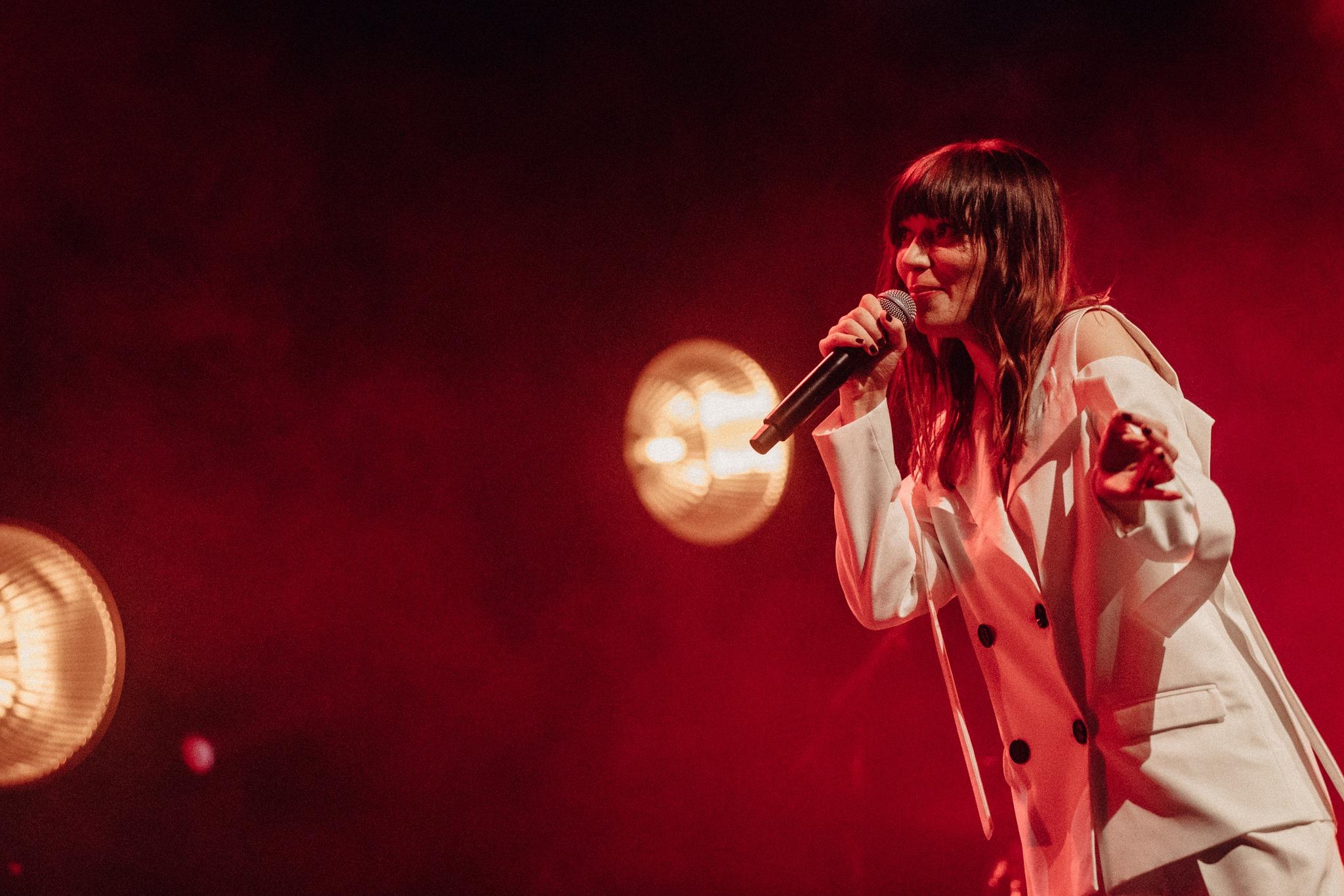 Zdjecie przedstawia koncert widzimy czerwone swiatlo a na jego tle do polowy kobiete brunetke ubrana w biala marynarke ma dlugie wlosy